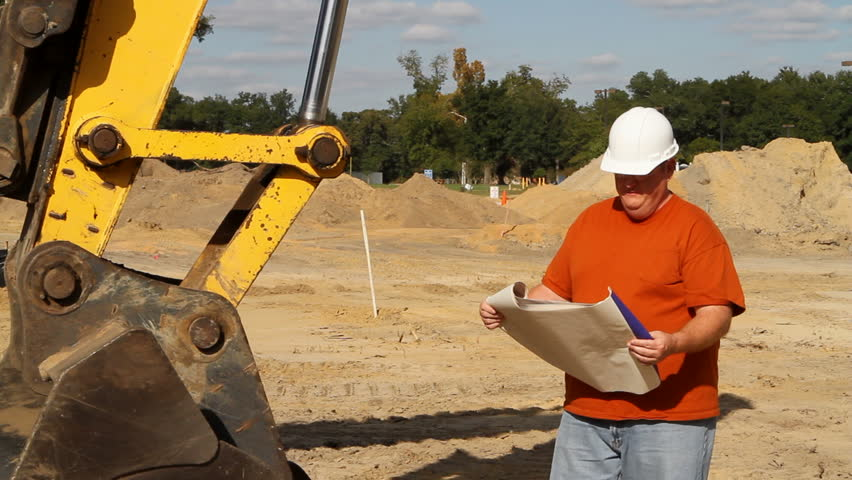 Construction foreman at an excavation site studies some blueprints and surveys the layout of the land. - HD stock footage clip