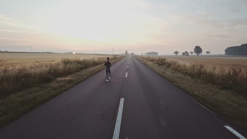 AERIAL 4K: Woman Running on a Countryside Road at Sunrise. Drone shot of a Female jogger athlete training at dusk. Active healthy lifestyle concept. Cinematic morning sports footage. | Shutterstock HD Video #29193766