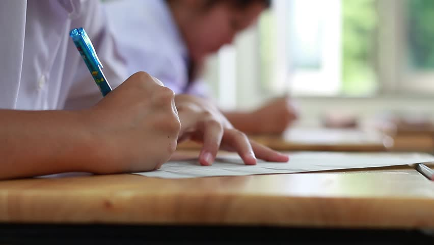 Blurred of Asian girl students groups sitting on row wood desk table with writing Exams paper sheet or test paper in high school with student uniform in tests class room, education concept, Thailand | Shutterstock HD Video #29219704