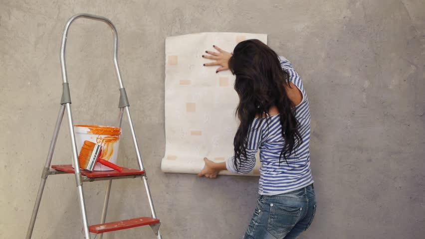 Beautiful woman gluing wallpaper on wall