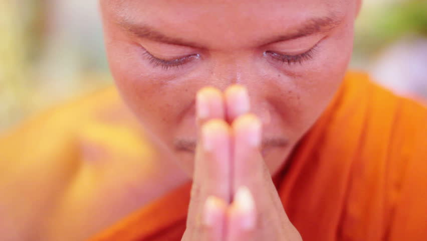 Buddhist monk with orange robe pray in temple with hands clasped