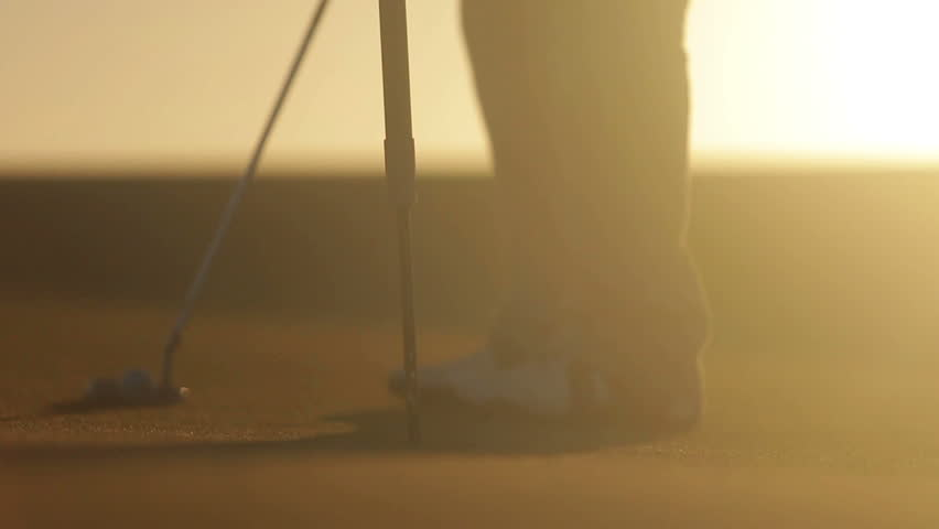 Man playing golf at sunset - HD stock footage clip