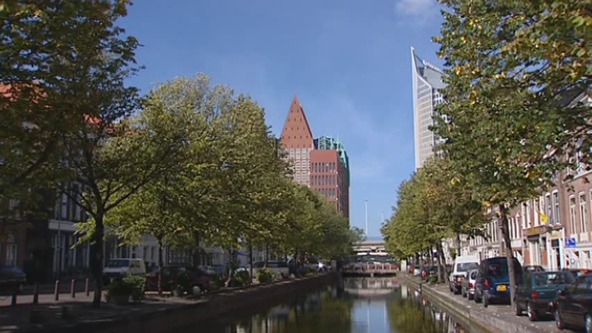 THE HAGUE, THE NETHERLANDS - SEPTEMBER 2003: central district, canal, quays, cars parked along canal +  tilt up tree - HD stock footage clip