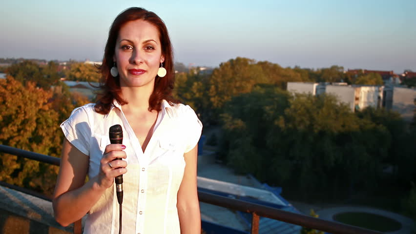 female TV reporter announces events in the city from the balcony of the building of television