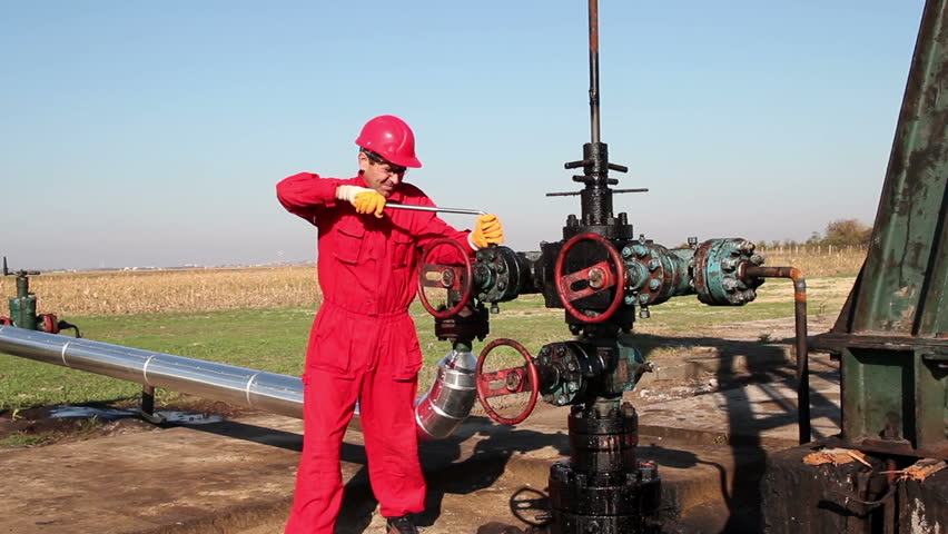 Man Working on Oil Field Equipment. Oil worker in action at oil well. HD1080p. - HD stock video clip