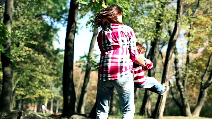 Young mother having fun with her son in beautiful autumn park, slow motion  - HD stock video clip