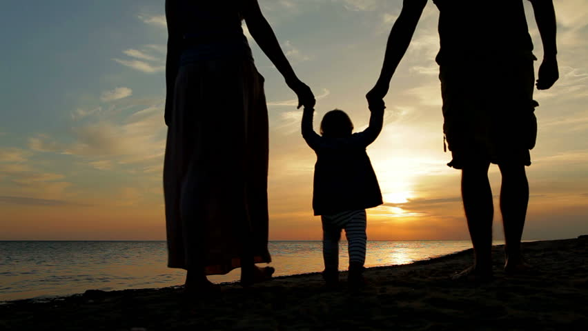 Happy family walking on sea coast. Silhouettes sunset. | Shutterstock HD Video #2980051