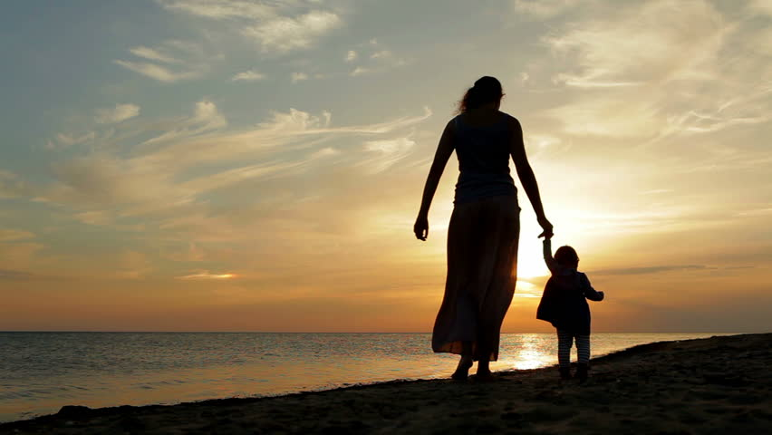 Mother with baby walking on sea coast. Silhouettes sunset. - HD stock footage clip