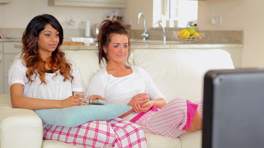 Women sitting on the couch in front of the TV - HD stock footage clip