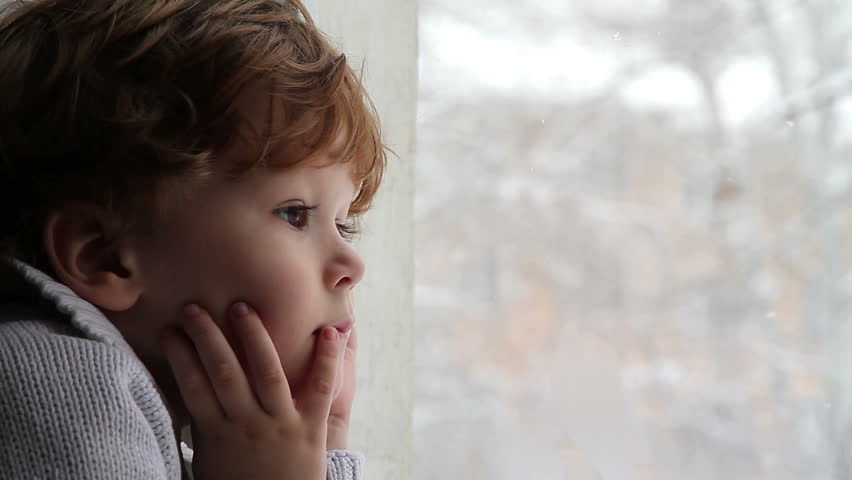 Boy looking out the window at the falling snow