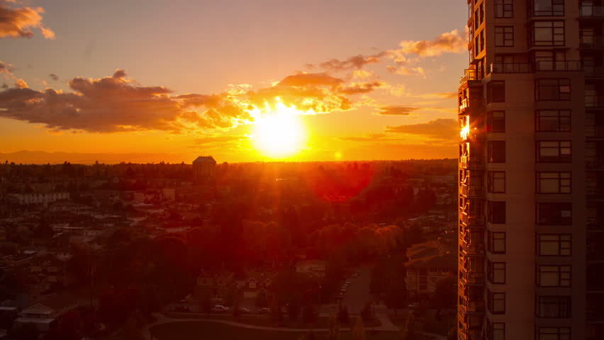 Time Lapse of Sunset in a Residential Area with Houses and Apartment. Sun light reflecting from apartment building as it setting down the horizon - HD stock video clip