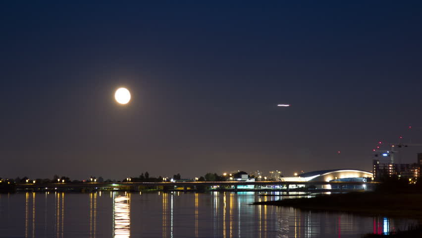 Moon Rising above the Richmond Olympic Oval in Richmond, BC, Canada. Airplane arriving to the Vancouver International Airport. Shot in 4k RAW photo sequence