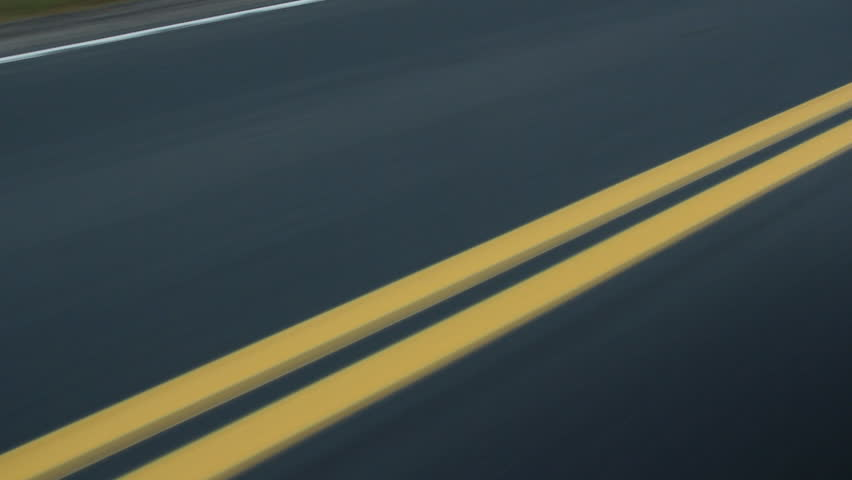 Double yellow lines on the road. Car passes. Ontario, Canada.