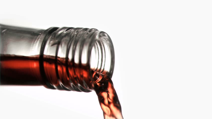 Close up, red liquid in a super slow motion flowing of the glass bottleneck against a white background - HD stock video clip