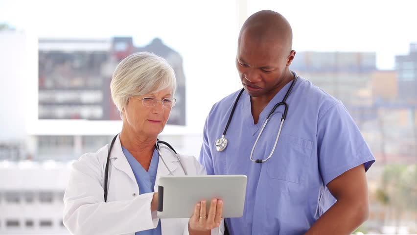 Happy doctor and nurse looking at a tablet pc in a bright room - HD stock video clip