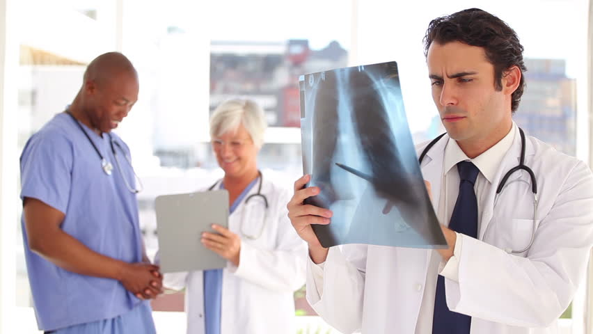 Smiling doctor looking at a chest x-ray in a bright office | Shutterstock HD Video #3048460