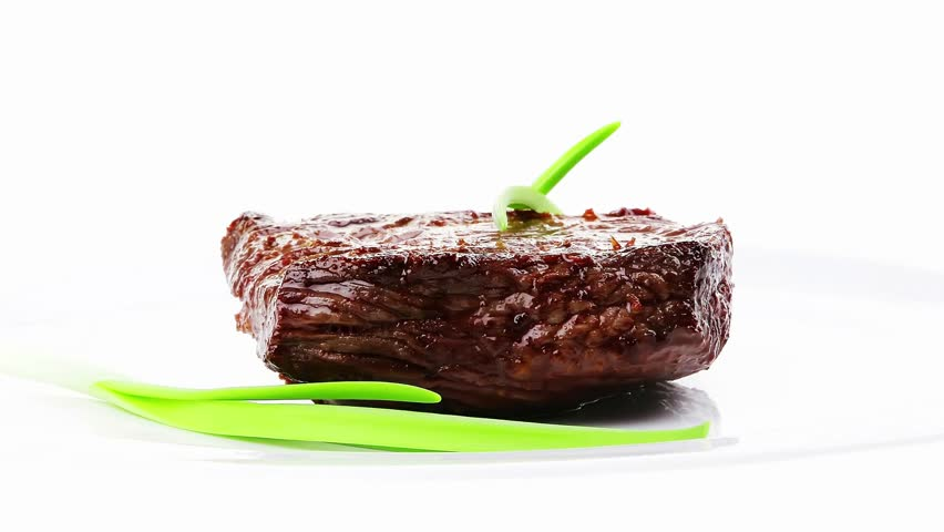 meat savory : grilled beef fillet mignon on white plate with green onion sprouts isolated over white background - HD stock video clip