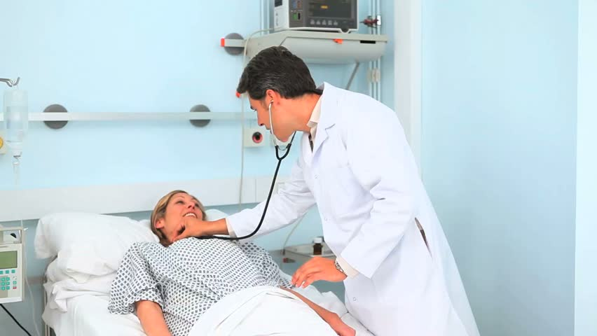 Doctor and patient smiling in hospital ward - HD stock video clip