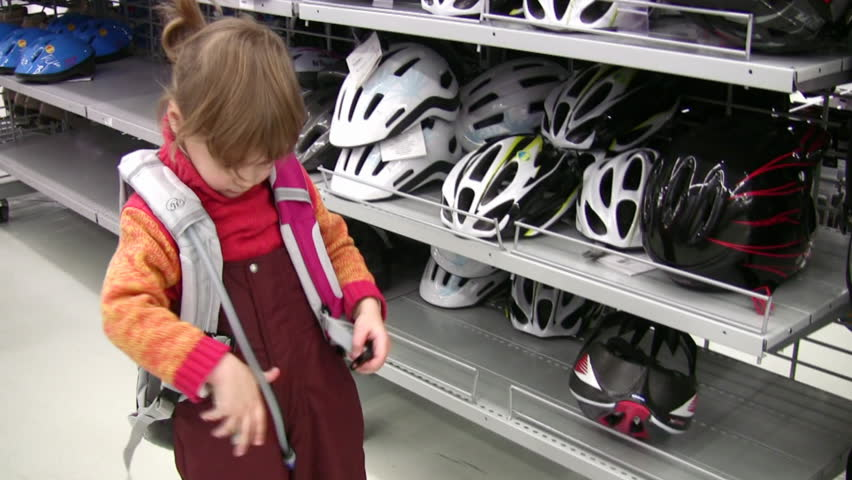 little girl with knapsack in shop, bicycle helmets