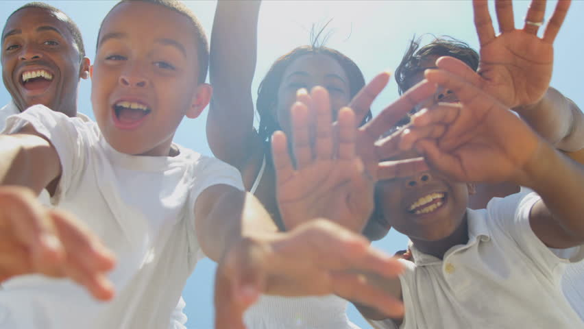 Close up of ethnic family waving on video call together on beach