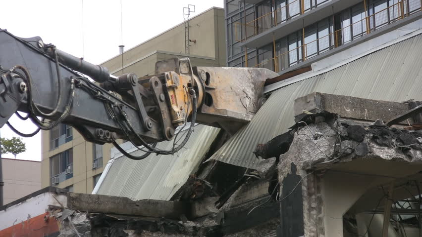 Demolition. Robotic claw destroys downtown building.  - HD stock footage clip