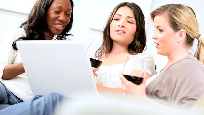 Multi ethnic women drinking red wine using laptop - HD stock footage clip