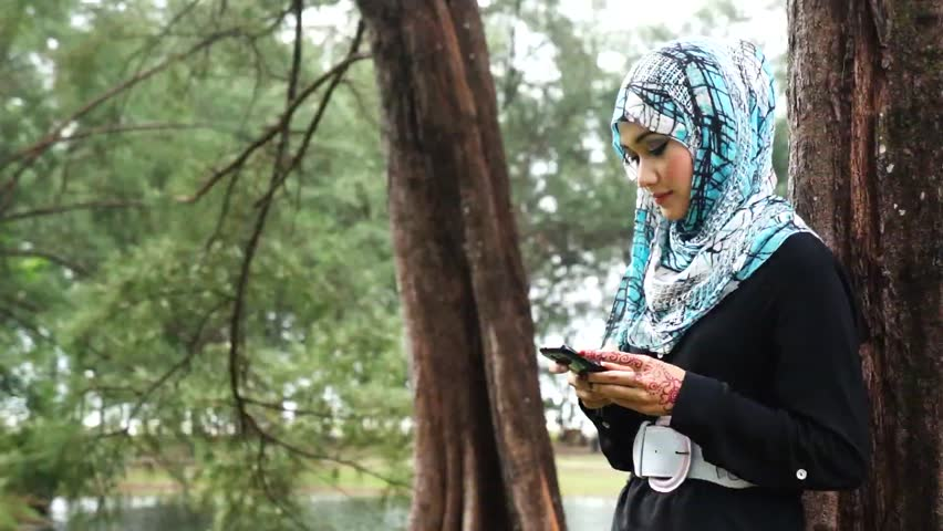 Beautiful muslim lady texting message on mobile phone - HD stock video clip