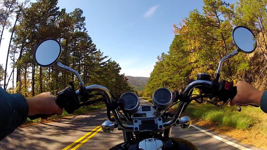 A wide angle point of view shot from a chest mounted camera on a motorcyclist riding a motorcycle on a forested mountain road. - HD stock footage clip