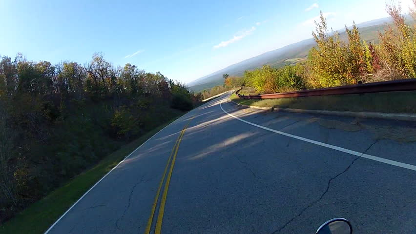 A helmet-cam POV shot of a motorcycle speeding down a curvy, forested mountain