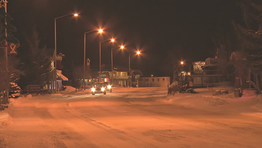 HOMER, AK - CIRCA 2012: Minimal traffic at night in a small town on snow-covered roads in the middle of winter. - HD stock video clip