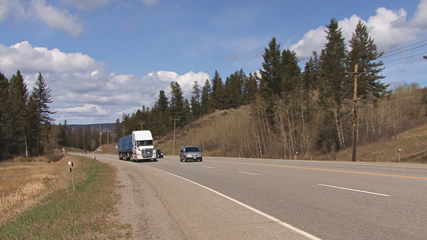 BRITISH COLUMBIA, CANADA - CIRCA 2012: Two tractor-trailer trucks pass by on the
