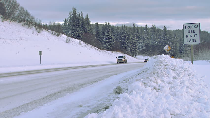 HOMER, AK - CIRCA 2012: Several vehicles being driven on a snowy Alaskan road in the winter time. Road signs show evidence of recent plow activity. - HD stock video clip