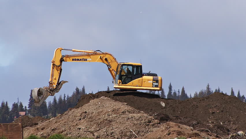 HOMER, AK - CIRCA 2012: Excavator working on mound of dirt, expanding land fill area. - HD stock video clip