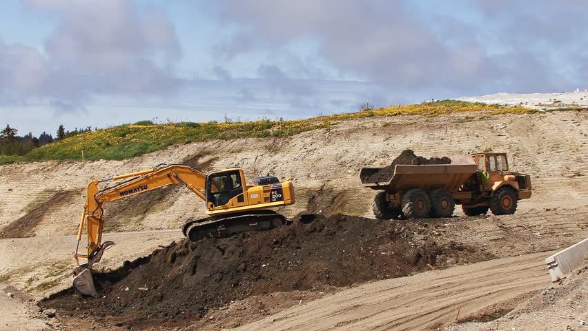 HOMER, AK - CIRCA 2012: Excavator and dump truck being operated as a team to move dirt from one place to another. - HD stock footage clip