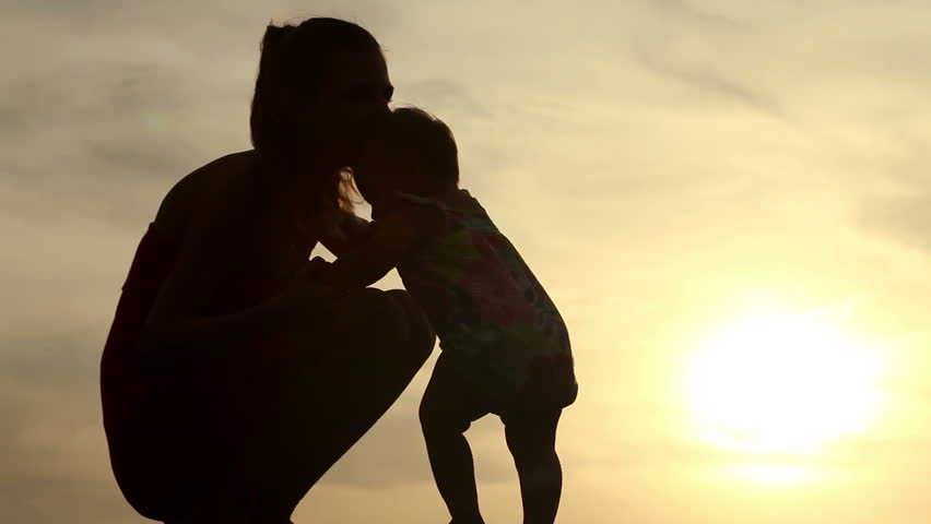 young mom nursing her baby in sunset light
