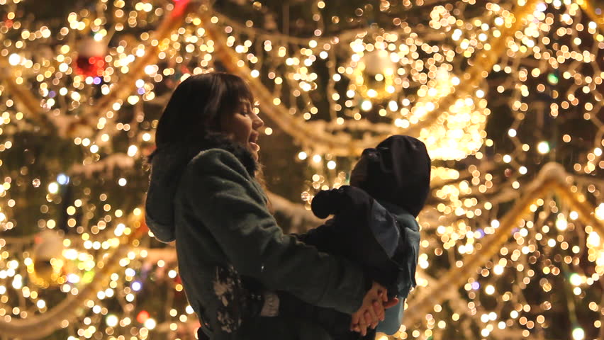 Mother and baby dancing and having fun during Christmas night in front of the decorated big tree full of colorful sparkling lights | Shutterstock HD Video #3168997