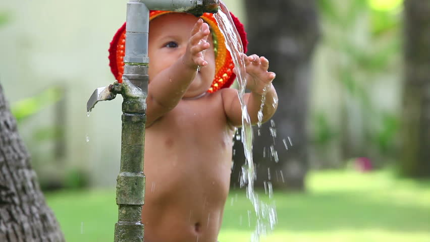 Cute small girl in hat playing with water | Shutterstock HD Video #3182569