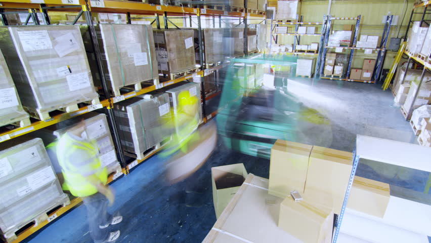 Time-lapse clip of workers in a warehouse in high visibility clothing and hard hats. They are moving boxes around and using a forklift truck to manoeuvre heavy stacks of goods around. - HD stock footage clip