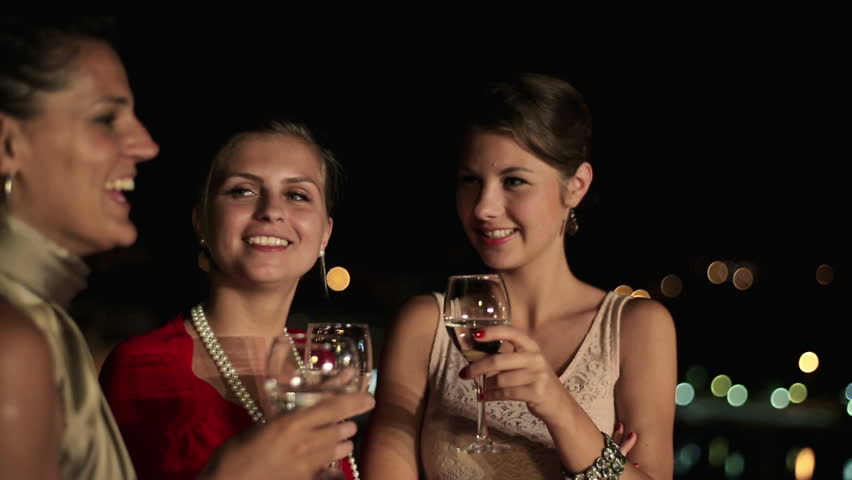 Happy girlfriends raising toast on party, steadicam shot