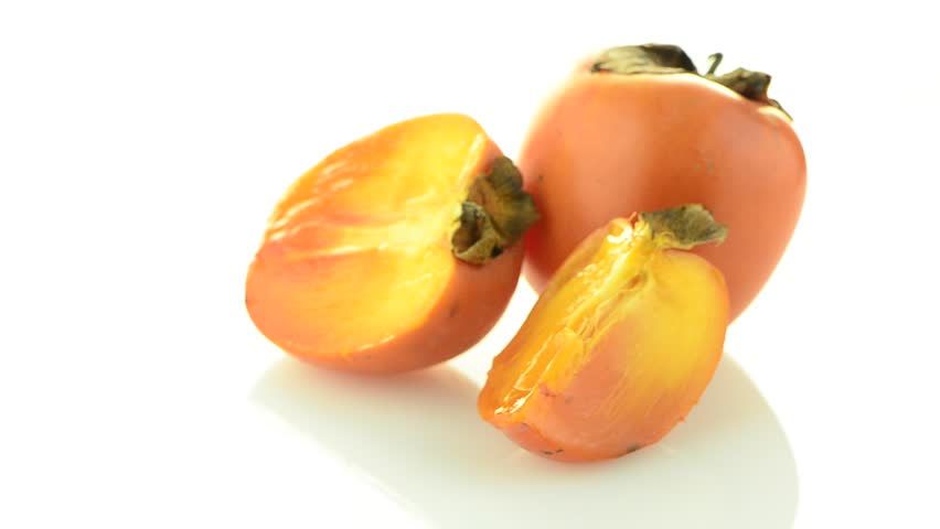 Red ripe persimmons rotating over white background. - HD stock video clip
