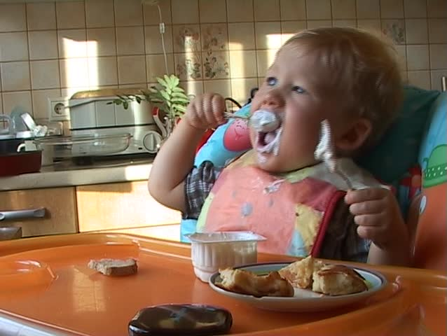 Baby learning to feed himself with a spoon and getting messy in the process