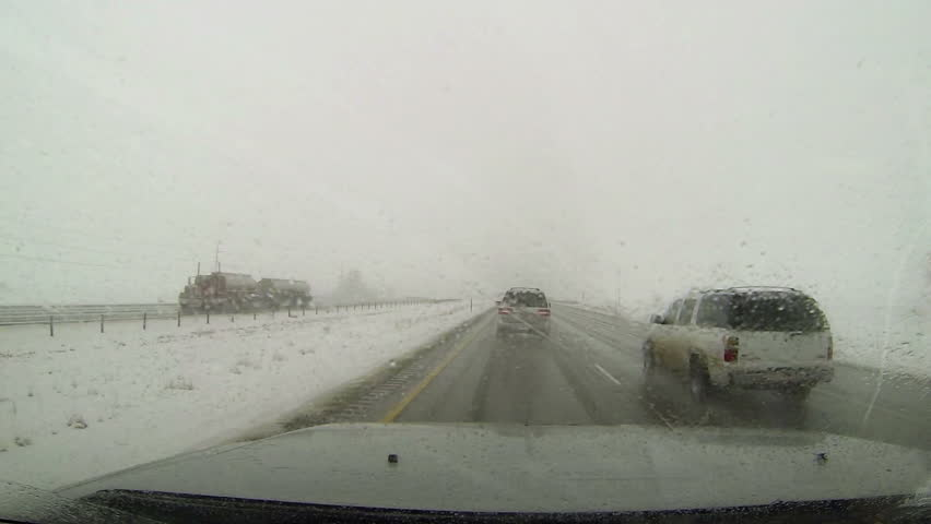 Winter storm snow rain driving Point Of View. Winter snow blizzard with ice and snow on road. First person point of view (POV) looking through drivers windshield. Urban freeway highway roads. | Shutterstock HD Video #3194701