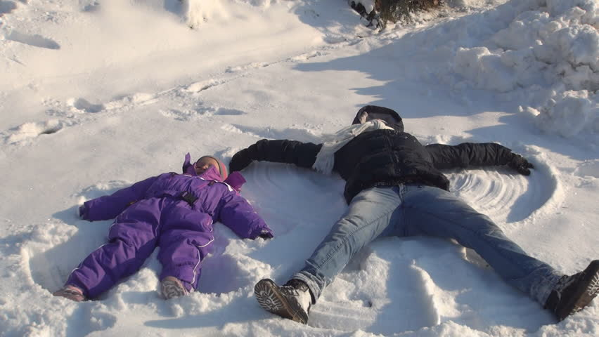 Mother and Child Making Angels in Snow, Family Playing in Snow - HD stock video clip