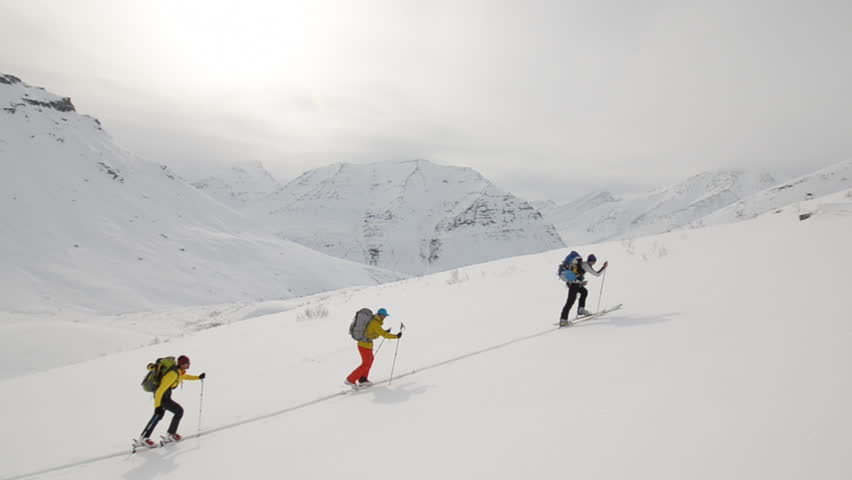 A group of backpack laden hikers ski up a dangerous snow and ice covered mountain face in Alaska during the day while the wind blows clouds around