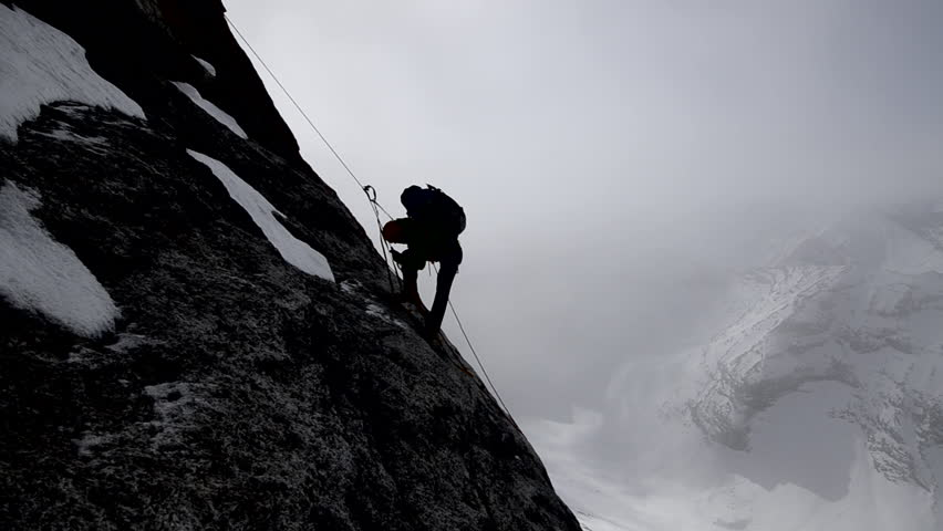 Silhouette of a climber with a backpack ascending a sheer rock face on his way to a mountain peak in the Alaskan wilderness during the day | Shutterstock HD Video #3201658