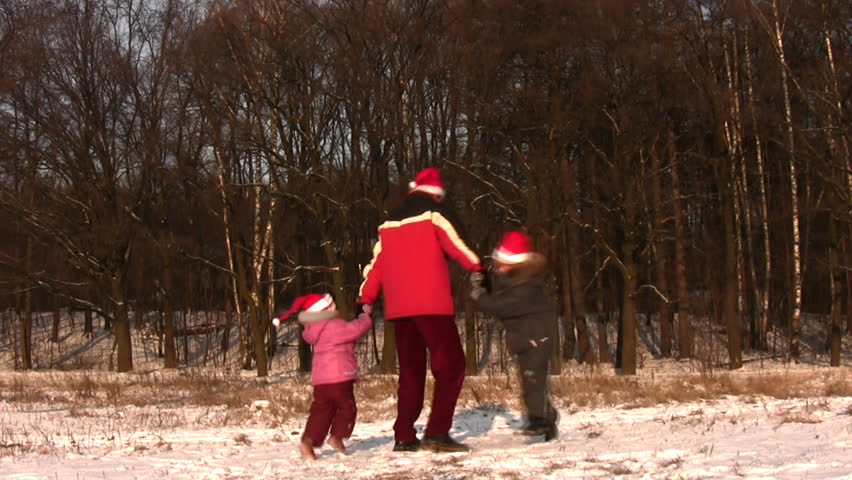 father rotating children in christmas hats  - HD stock video clip