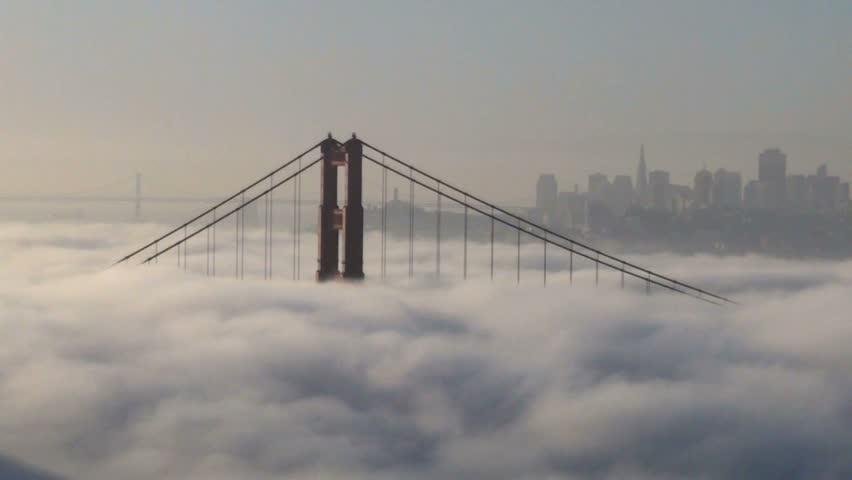 Fog flows over the Golden Gate Bridge at sunrise - San Francisco, California