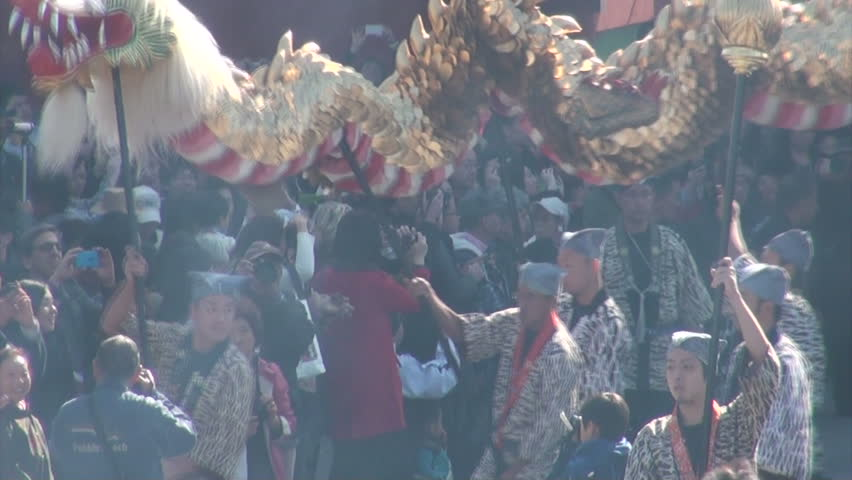 TOKYO, JAPAN - 3 NOVEMBER 2012: Japanese devotees are carrying a large dragon through the streets while smoke coming from an incense burner blurs their vision at the Sensoji temple complex in Tokyo - HD stock video clip