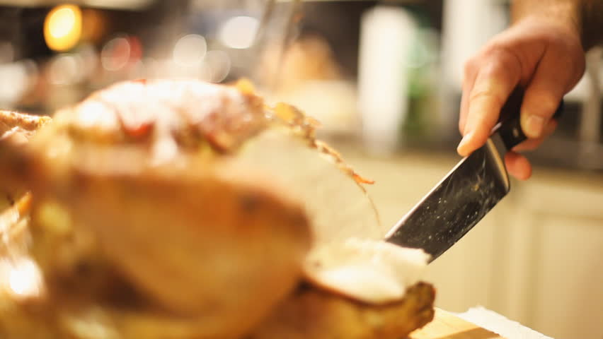 Man Carves Turkey With A Chefs Knife Cutting The Breast Meat For A Christmas Or Thanksgiving Celebration Meal