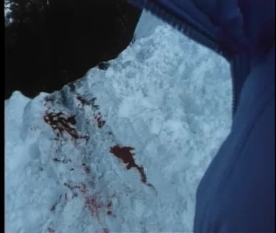 Point of view shot of bloodstains on a snowy cliff